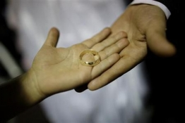 two-hands-holding-a-wedding-ring